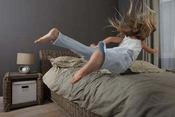 Enfant saute sur un lit