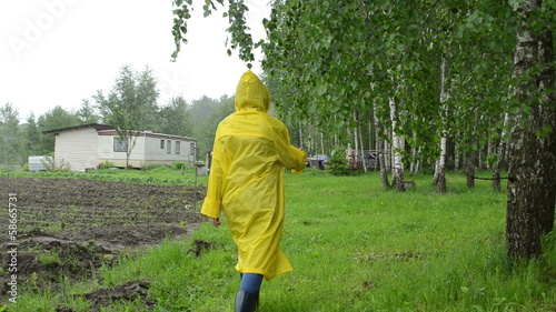 Woman in waterproof coat near birch tree and small garden house
