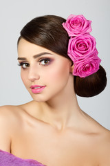 Beautiful young woman with pink roses in her hair