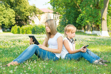 Boy and girl sitting in park with digital tablet
