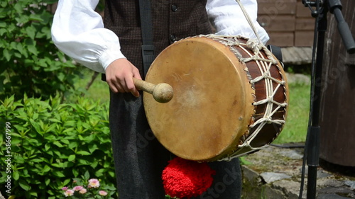 Drummer play folk music with drum and stick in village party
