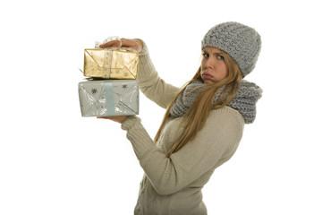 Frau warm angezogen trägt schwere Weihnachtsgeschenke