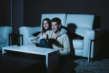 Young couple in love watching TV late at night