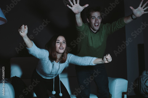 Young couple cheering for a sport team watching sports on TV