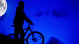 Bicycle night rider goes home in moonlight