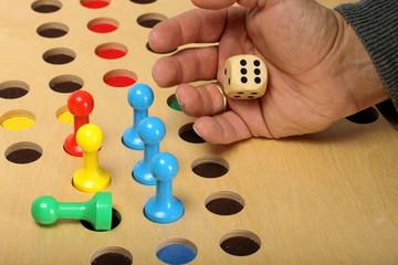 aus Hand fällt Würfel auf hölzernes Spielfeld
