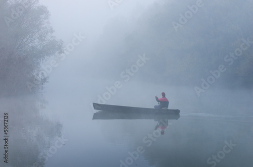 Man rowing in a boat on foggy morning