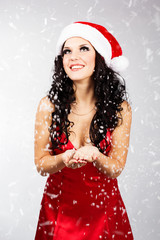 Pretty Santa woman with snow in her hands