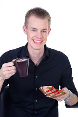 Junger Mann mit belegtem Brot zum Frühstück
