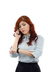 Business woman looking at her watch while talking on the phone