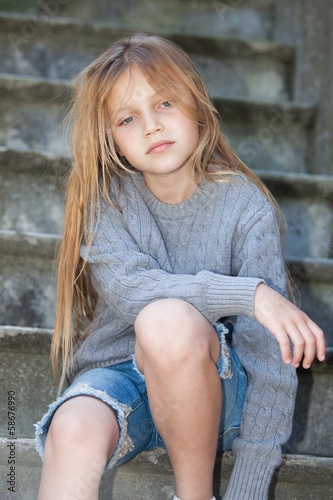 sad little girl sitting on the stairs