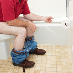 Man Using Toilet Paper in Bathroom