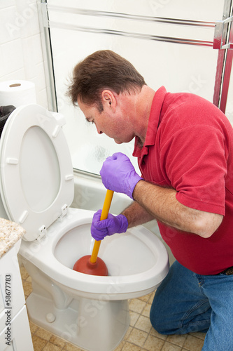 Man Using Plunger in Toilet