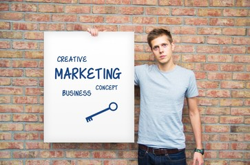 Young man holding whiteboard with marketing content. Business pr