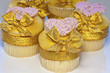 Iced cup cakes decorated with golden bows and pink hearts.