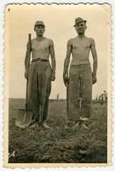 CIRCA 1940: Two young men (probably in military trousers)