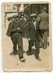 CIRCA 1930: Two young men walking around town