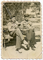 CIRCA 1935: Young men in uniform sitting on a park bench
