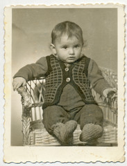 CIRCA 1950 - Portrait of sitting baby on wicket chair
