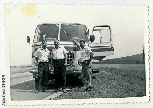 CIRCA 1960: Men standing in front of the bus, on the road
