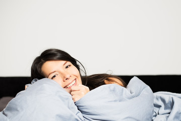 Laughing woman snuggling up in her bed