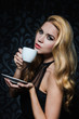 Beautiful Woman enjoying  cup of Coffee.Isolated on black