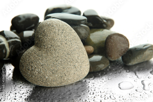 Grey stone in shape of heart, on light background © Africa Studio