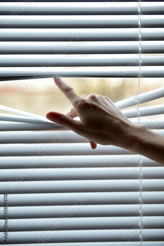 Female hand separating slats of venetian blinds with a finger