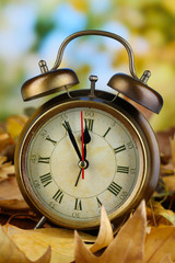 Old clock on autumn leaves on wooden table on natural