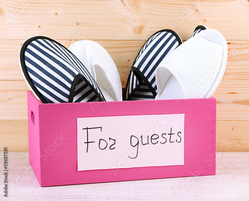 Slippers in wooden box on table on wooden background