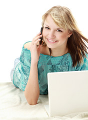 A young woman lying  with a laptop and talking on the phone