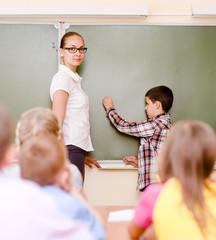 boy answers questions of teachers near a school board