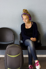 Girl with headphones waiting to travel