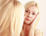 Woman caring of her skin on the face standing near mirror.