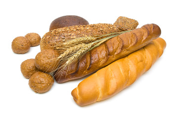 Fresh bread and wheat ears on white background
