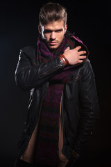 young man in leather jacket adjusting his scarf