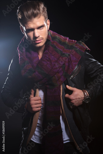 young man adjusting his leather jacket