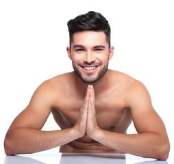 young smiling man is praying