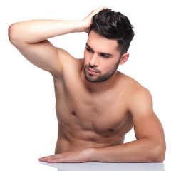 man passing his hand through his hair and looking away