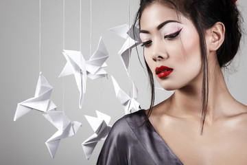 Young beautiful asian woman with origami paper pigeons
