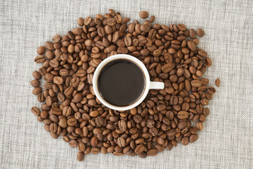 Cup with coffee and coffee grains.