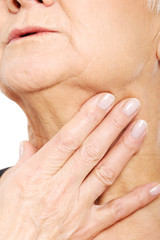 Close up on older woman's hand holding neck.