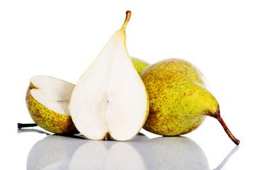 Fresh greeny pears divided into two over white.