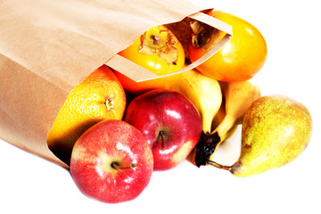 Apples,kaki and pears lying on the floor in paper bag.