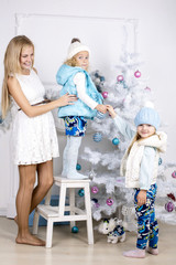 mother with litle daughters are decorating Christmas Tree