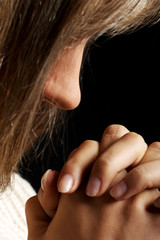 Young woman praying, close up.
