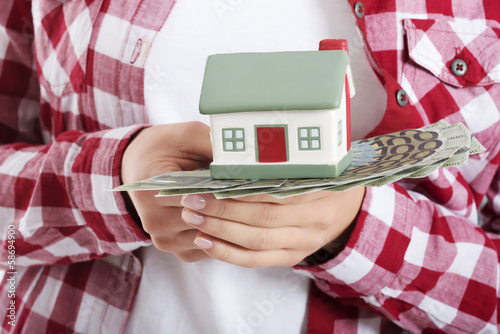 Casual woman holding money and house on hands.