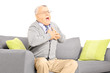 Senior man seated on a sofa having a heart attack