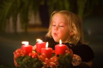 Kind mit Adventskranz zu Weihnachten