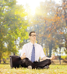 Young businessperson seated on a grass meditating in a park
